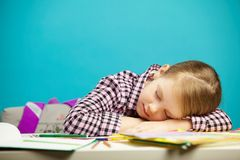 Isolated portrait of sweet sleeping girl at desk during class or hometask. Tired child fell asleep in school. Absent mindedness and forgetfulness of people Royalty Free Stock Photos