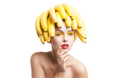Isolated portrait of topless model with bananas on head. Beautiful fragile model with bunch of bananas on head looking away.Studio shot Royalty Free Stock Photos