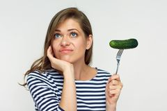 Isolated portrait of woman holding cucumber on fork. Dieting is not always fun. Isolated portrait of woman holding cucumber on fork Stock Photography