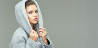 Isolated portrait of young beauty woman wearing gray coat. With big hood Royalty Free Stock Image