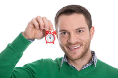 Isolated portrait of young male with miniature alarm clock. Stock Photos