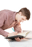 Isolated portrait of young man writing in notebook Royalty Free Stock Image
