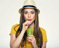 Portrait of young woman drinking juice. Isolated portrait of young woman drinking juice with straw Stock Image