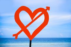 Isolated post signal with red love heart and arrow at beach on a blue sea and sky background in Valentines day and romance concept. Ual Royalty Free Stock Images