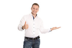 Isolated presenting young smiling man with palm and thumb up ges Stock Photo