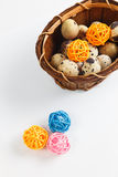 Isolated quail eggs in a basket with decorative wooden balls. Still Life with quail eggs in a basket with decorative wooden balls isolated on white background Royalty Free Stock Image