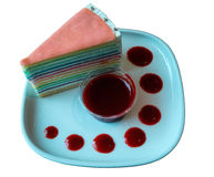 Isolated rainbow crape cake. With strawberry sauce on the white plate Royalty Free Stock Photo