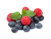 Isolated raspberries and blueberries. Fresh raspberries and blueberries lying on a white background Royalty Free Stock Photos