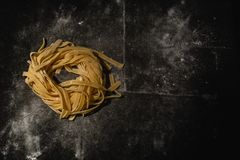 Isolated raw pasta on a black background with a place for text. Traditional Italian pasta, noodles, tagliatelle. Top view. Copy royalty free stock images