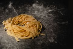 Isolated raw pasta on a black background with a place for text. Traditional Italian pasta, noodles, tagliatelle. Top view. Copy stock images
