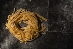 Isolated raw pasta on a black background with a place for text. Traditional Italian pasta, noodles, tagliatelle. Top view. Copy royalty free stock photos