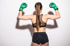 isolated rear view white Stående av den säkra unga idrottsman nenkvinnan för tillbaka sida som poserar i boxninggräsplanhandskar  royaltyfri foto