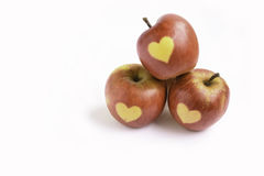 Isolated red apples with shape of heart on a white background Stock Photos