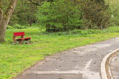 Isolated red bench in the park near an asphalt road Germany, Europe stock photography