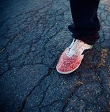 Isolated red coloured shoes on a street. A red coloured shoes on a concrete streets isolated unique photo royalty free stock image