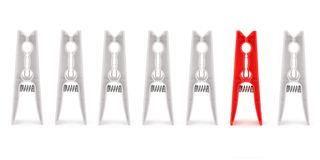 Isolated red peg among white ones. Isolated red peg among six white ones stock photography