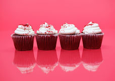 Isolated Red Velvet Cupcakes on Background. Image of four Red Velvet Cupcakes isolated on a red background Stock Photo