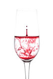 Isolated of red water drop to wine glass is still on white backg Stock Photos