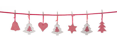 Isolated red and white christmas decoration hanging on a line. Isolated red and white christmas decoration hanging on a line with clothespins royalty free stock photography