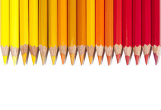 Isolated red yellow and orange pencils in line Royalty Free Stock Photography