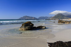 Isolated rocks on sandy beach. With mountain backdrop Royalty Free Stock Image