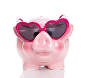 Isolated rose piggy bank with heart glasses on white background Royalty Free Stock Photos