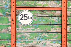 Isolated round metal speed limit 25 km sign on weathered colorful wooden planks with peeling paint on back of agricultural trailer stock photography