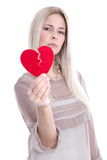 Isolated sad blond caucasian woman holding broken red heart - lo Stock Photo