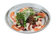 Isolated Salmon and shrimp salad with red oak, pea, crouton with mayonnaise topping with wild rocket in ink painted ceramic bowl Stock Image