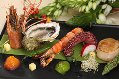 Isolated seafood set on black plate. Close up Stock Photo