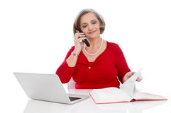 Isolated senior business woman in red calling - sitting at desk. Stock Image