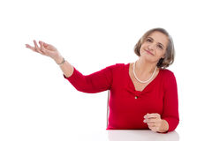 Isolated senior business woman in red presenting with hand. Stock Image