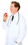 Isolated Senior Caucasian Doctor Eating Apple Stock Photography
