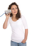 Isolated serious woman listening on tin can phone for news or ch Royalty Free Stock Image