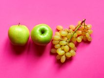 Isolated set of a green apple with a bunch of sweet seedless grapes in studio with pink background. Above view of isolated set of a green apple with a bunch of stock photo