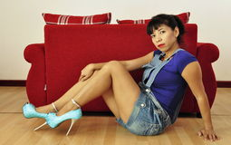 Isolated shot of Asian woman sitting on floor Stock Images