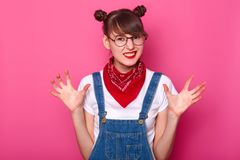 Isolated shot of attractive brunette pretty teenager, wears denim overalls, white casual t shirt, red bandana on nack, looking at royalty free stock image