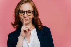 Isolated shot of attractive secret woman keeps fore finger over lips, demonstrates shush gesture, tells secret information, has stock images