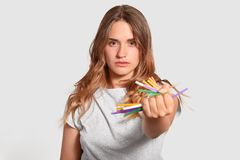 Isolated shot of attractive serious girl bans using plastic tubes, refuses of pollution, has determined facial expression, stands. Indoor, demands save earth stock image
