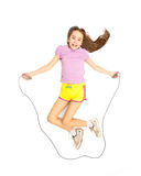 Isolated shot of cute active girl jumping with skipping rope Stock Photos