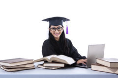 An isolated shot of female graduate with laptop and books Royalty Free Stock Photography