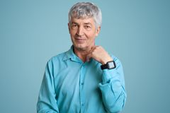 Isolated shot of handsome senior man wears blue elegant shirt, wrist watch, has wrinkled face, poses over blue background, looks. Directly at camera. Attractive royalty free stock photo