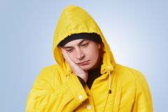 Isolated shot of pensive thoughtful man looks unhappily down, has toothache, keeps hand on cheek, wears yellow anorak with hood. U. Pset human analyzes his stock photography