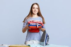 Isolated shot of pretty female with long hair, keeps pile with laundry, going to iron with electric iron, isolated over blue backg. Round. Beautiful woman busy royalty free stock image
