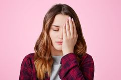 Isolated shot of pretty frustrated overworked female covers face with hand, keeps eyes shut, being sleepy, feels bored as spends t. Ime alone, poses against pink Royalty Free Stock Photos