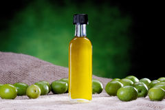 Isolated small bottle of olive oil with olives Stock Photo