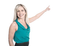 Isolated smiling woman in green shirt pointing at white. Royalty Free Stock Images