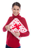 Isolated smiling young woman in red holding a present in her han Stock Photo