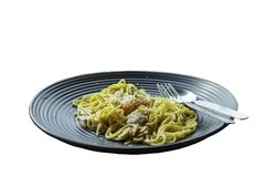 Isolated spaghetti, fried cheese on a black plate on a white ba stock photography