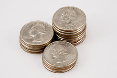 Isolated stacks of quarters. Three stacks of quarters in various heights Royalty Free Stock Photography